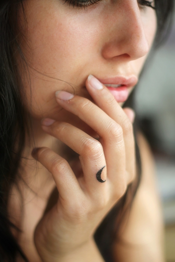 woman holding her hand, next to her face, small crescent moon, ring finger tattoo, finger tattoos for men