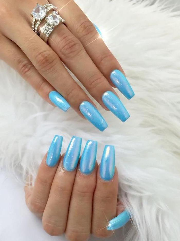blue metallic nail polish, long coffin nails, pink nail designs, two diamond rings on the middle finger