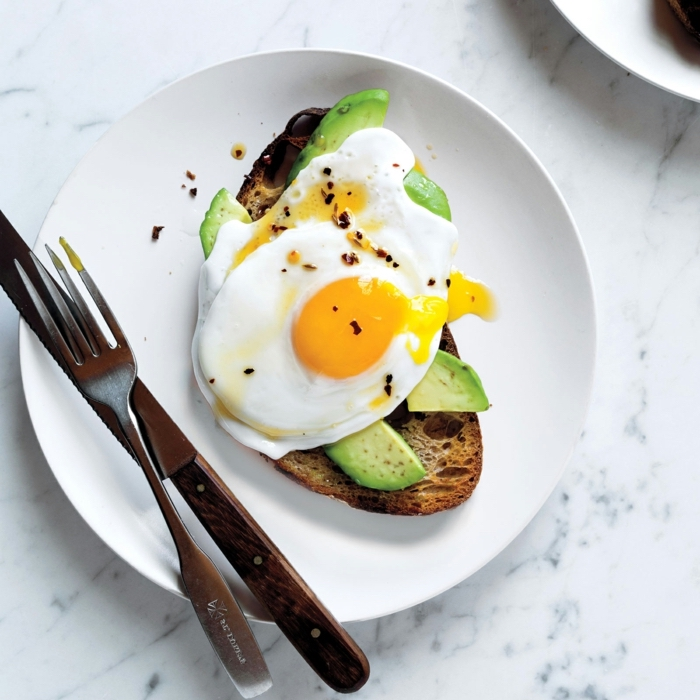 toasted bread, with avocado slices, eggs on top, balanced meal, on a white plate, knife and fork on the side