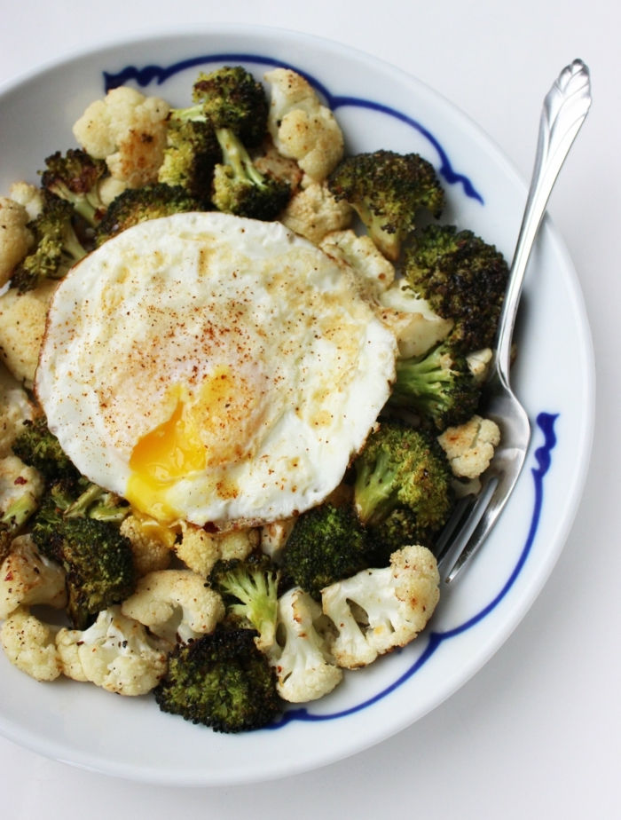 broccoli and cauliflower salad, with an egg on top, diets for women, in a blue and white bowl