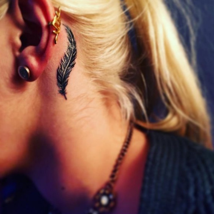 black feather behind the year tattoo, woman with a blonde hair in a ponytail, small meaningful tattoos
