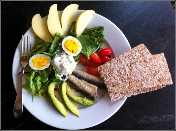 diets for women, white plate, full of green salad, fish and vegetables, boiled egg, apple slices