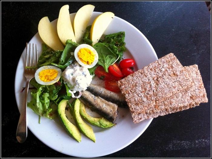 diets for women, white plate, full of green salad, fish and vegetables, boiled egg, apple slices