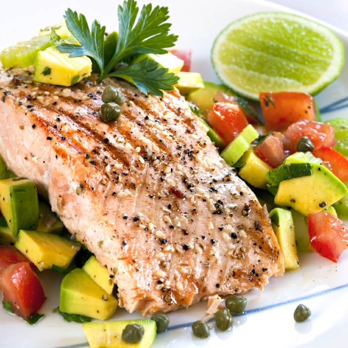 fish fillet, on an avocado salad, with tomatoes and capers, lime slice on the side, diets for women