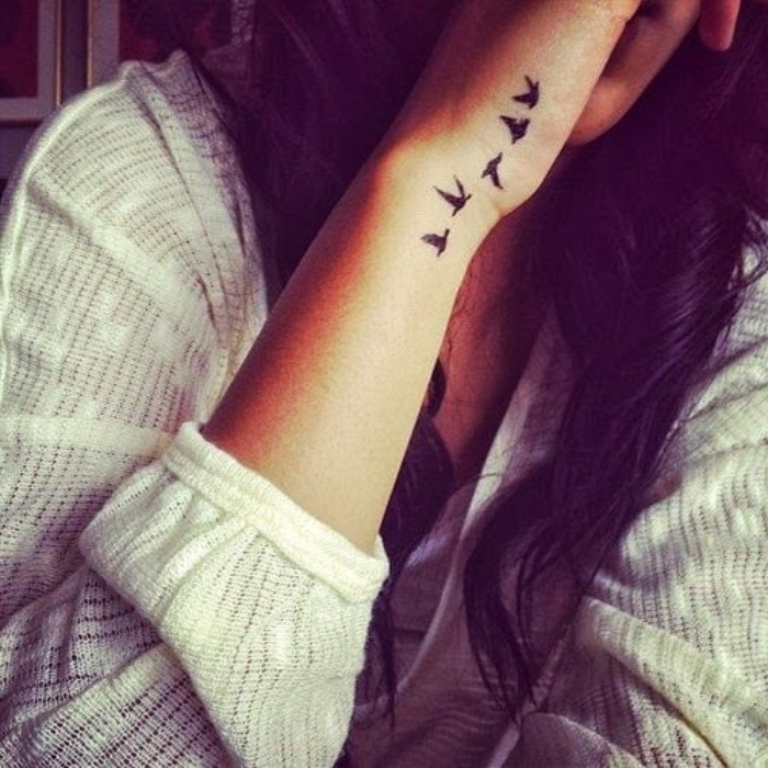 five birds flying away wrist tattoo, small meaningful tattoos, woman with long black hair, wearing a white blouse