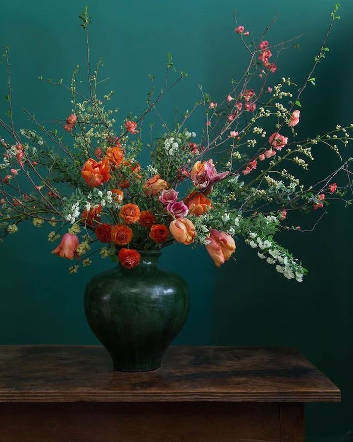 large vintage ceramic vase, colourful flowers bouquet, floral centerpieces, in front of a turquoise background