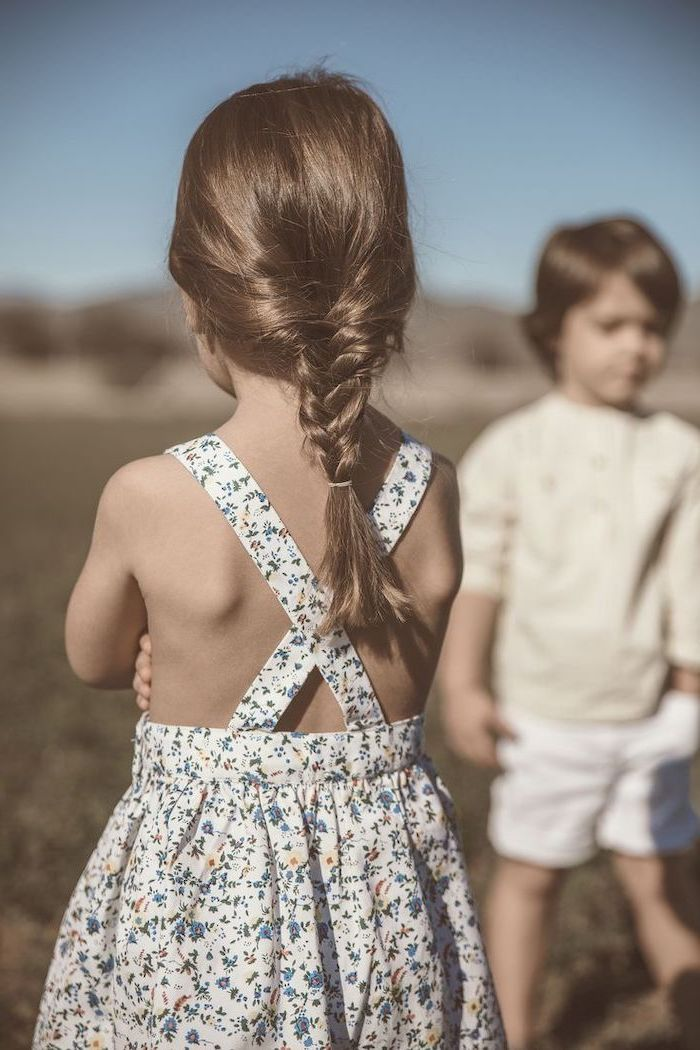 floral dress, little boy in the background, brown hair in a low braid, short hairstyles for girls