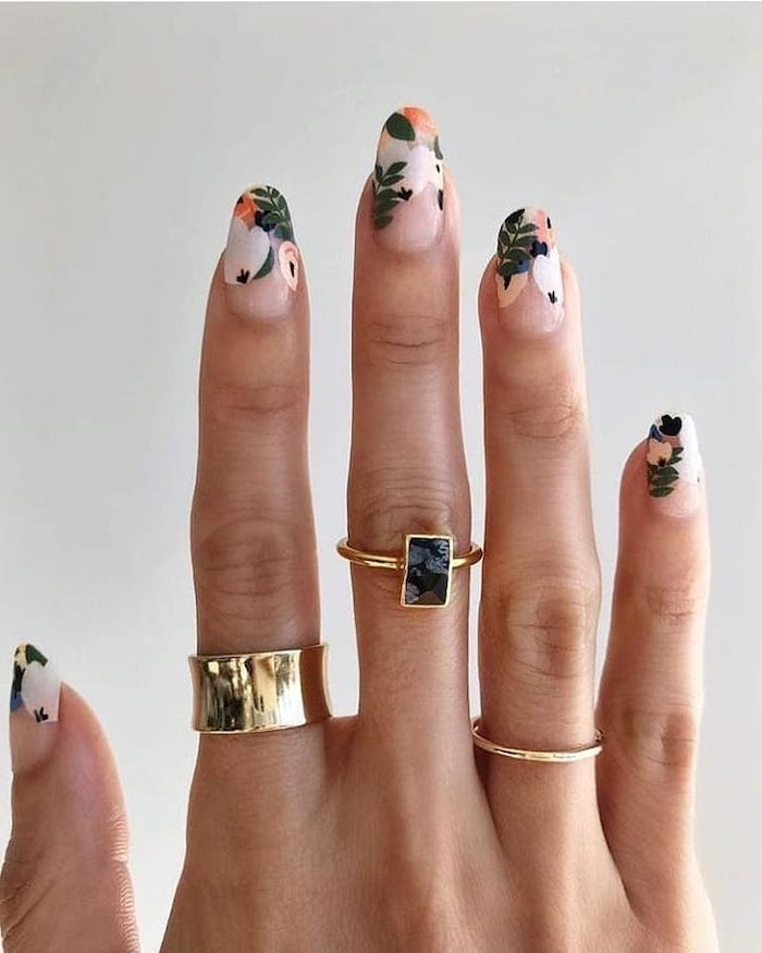 three golden rings on the finger, long almond shaped nails, nail design ideas, floral manicure