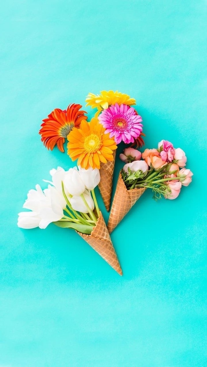 three different flower bouquets, in three ice cream cones, blue phone background, spring photos