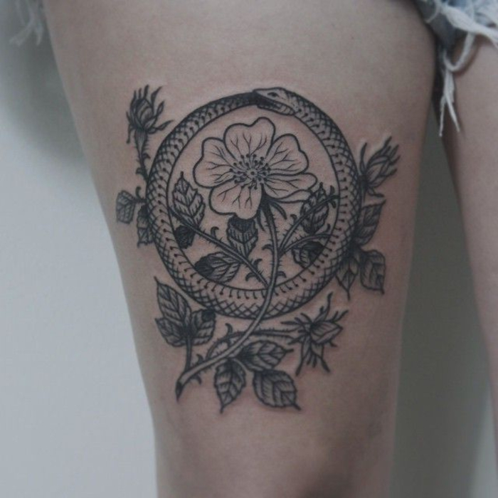 flower with thorns, snake eating itself, balance tattoo, on the girl's thigh