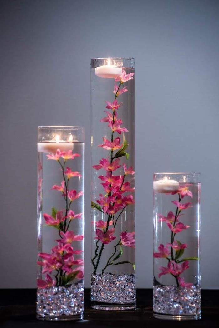 three tall round vases, flowers and candles, floating in the water, silk floral arrangements