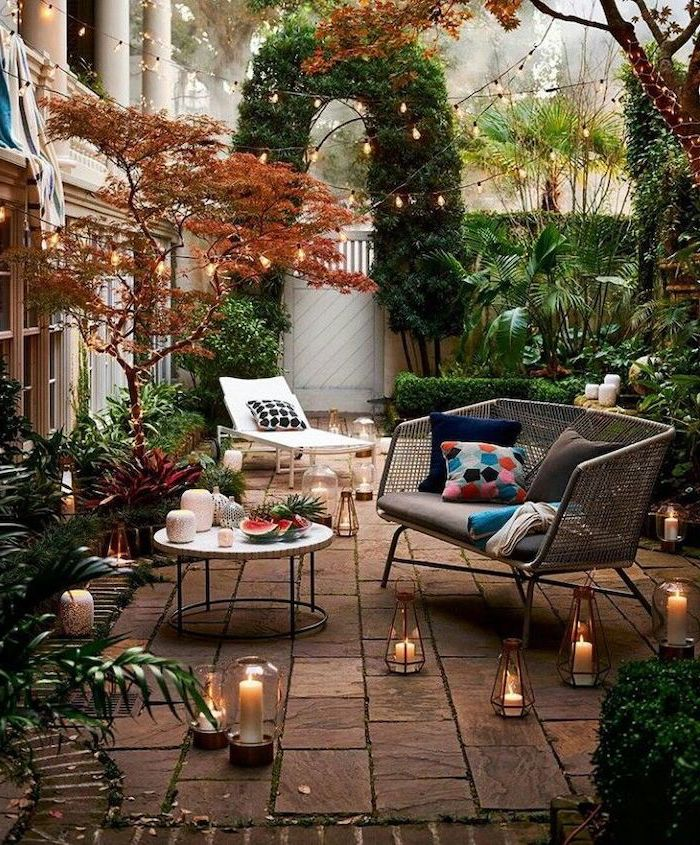 strings of lights, over the garden furniture, with colourful throw pillows, small backyard landscaping ideas
