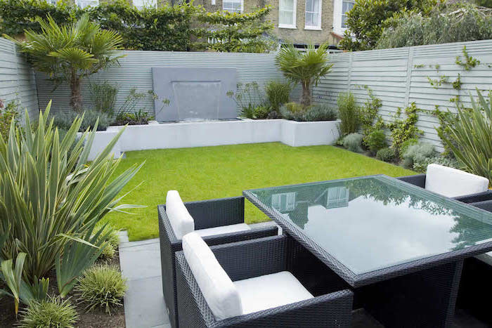 patch of grass, planted palm trees and bushes, garden design ideas, garden furniture, small fountain
