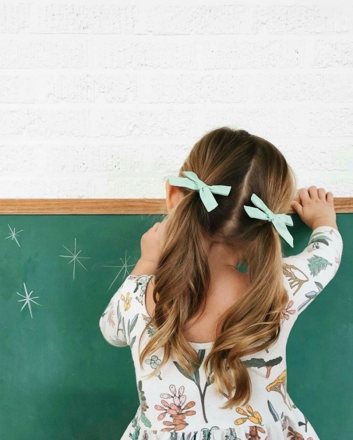 two mint green bows, brown hair in two low ponytails, cute hairstyles for little girls, green chalkboard