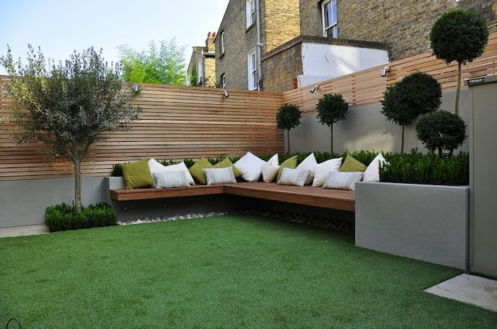 patch of grass, wooden bench, with white and green throw pillows, garden design ideas, planted trees and bushes