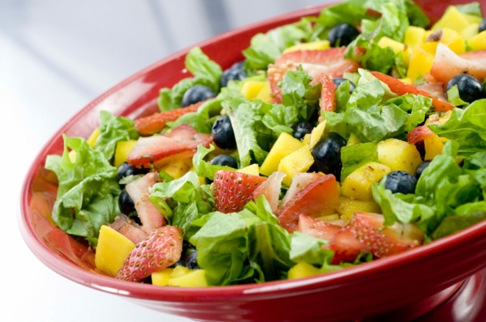 red salad bowl, full of green salad, strawberries and pineapple, fruit salad, healthy diet foods