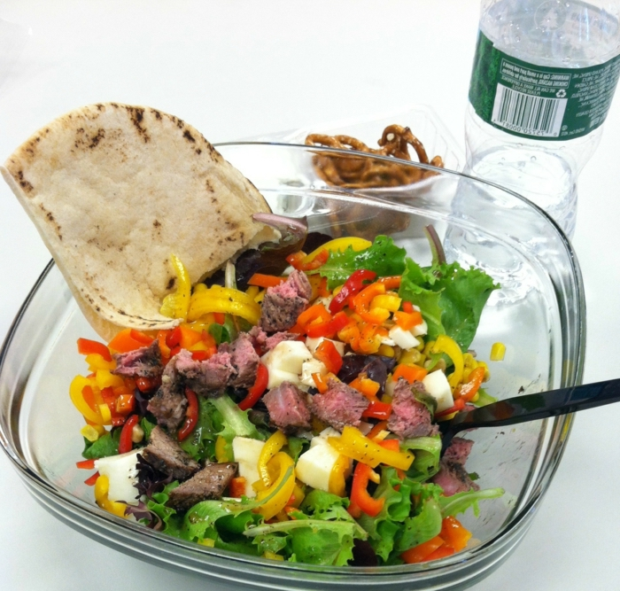 glass salad bowl, full of green salad, peppers and eggs, chopped red meat, healthy diet foods