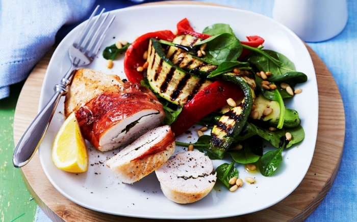 chicken fillet, grilled vegetables, basil and lemon slice on the side, best diet for women, in a white plate