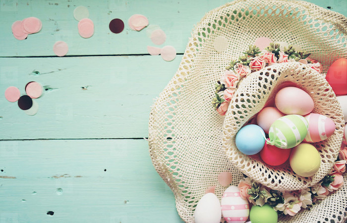 colourful dyed eggs, inside a hat, with flowers on the side, dying easter eggs with food coloring, turquoise backgorund
