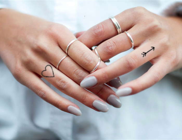 heart and arrow, ring finger tattoos, small finger tattoos, grey nail polish, silver stackable rings