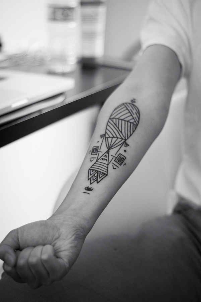 geometric animal tattoos, geometrical hot air balloon, on the forearm, man sitting down
