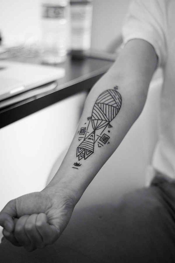 geometric animal tattoos, geometrical hot air balloon, on the forearm, man sitting down