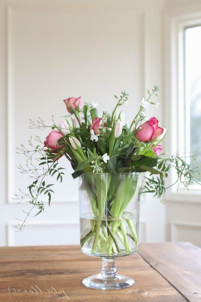 pink roses and white tulips, small bouquet, in a large round vase, silk floral arrangements, on a wooden table
