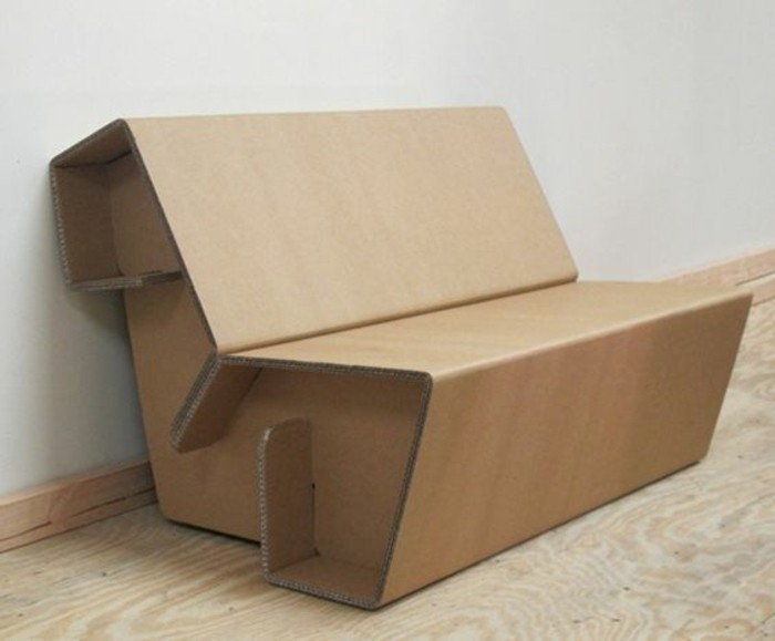 cardboard sofa, on a wooden floor, cardboard chair, in front of a white wall