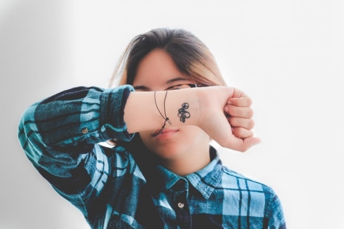 inscription wrist tattoo, woman wearing a blue plaid shirt, with brown hair, small bestfriend tattoos