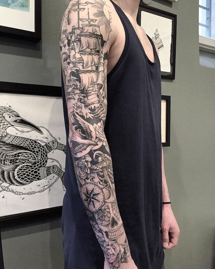 sailing inspired, arm sleeve tattoo, tattoo designs for men, man wearing a black top, standing in front of framed pictures