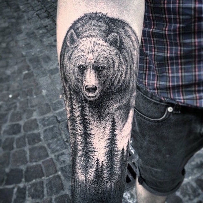 large bear, over a forest, forearm tattoo, tattoo designs for men, paved street, plaid shirt and jeans