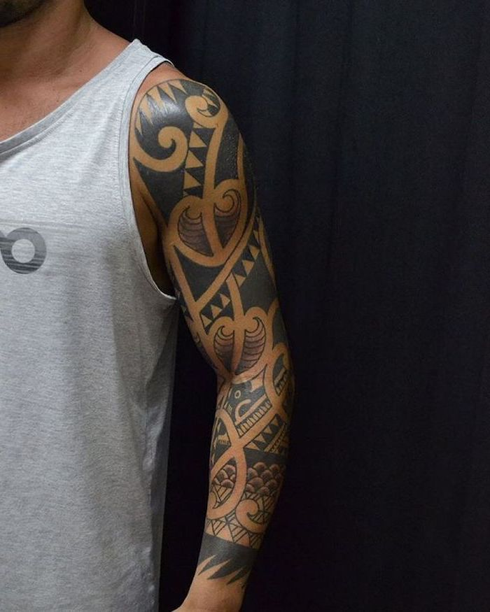 black and white, arm sleeve tattoo, man wearing a grey top, in front of a black background, tattoo designs for men