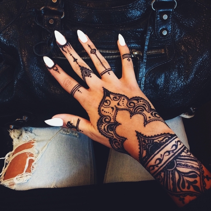 large henna tattoo, white stiletto nails, small finger tattoos, hand resting on a black leather bag