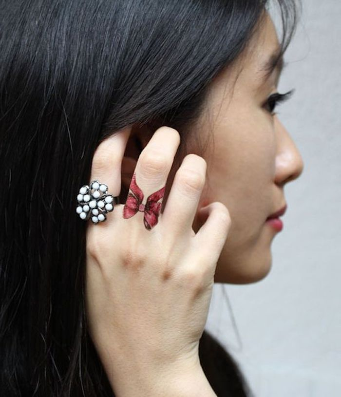 woman holding her black hair, white pearl ring, red bow, middle finger tattoo, finger tattoos for women