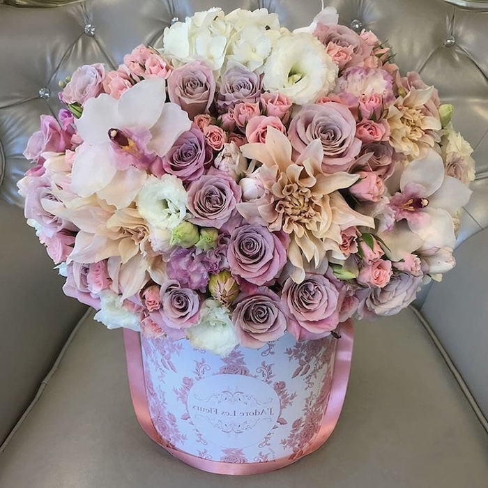 pink purple and white flowers, large flower bouquet, in a carton box, silk floral arrangements, on a grey leather sofa