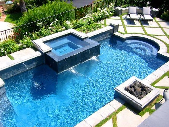 large pool, with a small hot tub, garden patio ideas, cement tiles, two grey lounge chairs, planted flowers