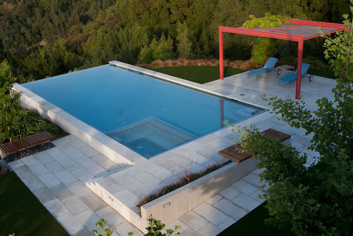 small pool, two blue lounge chairs, tiled floor, garden patio ideas, planted flowers and trees