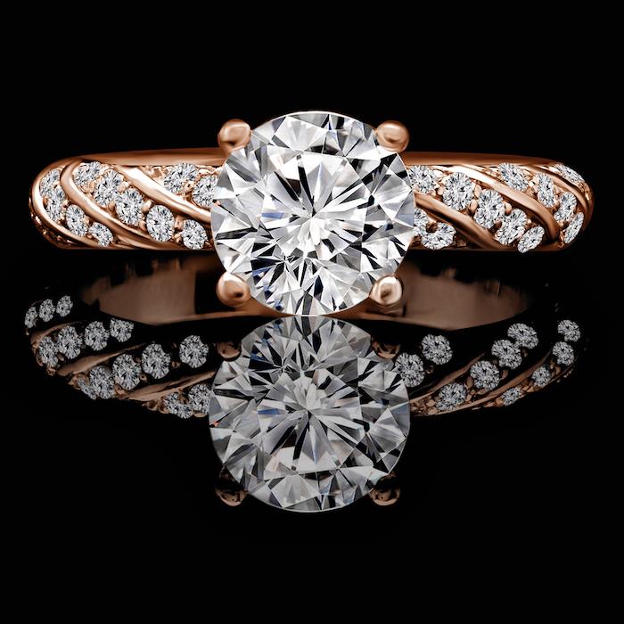 large round diamond, diamond studded rose gold band, teardrop engagement ring, black background