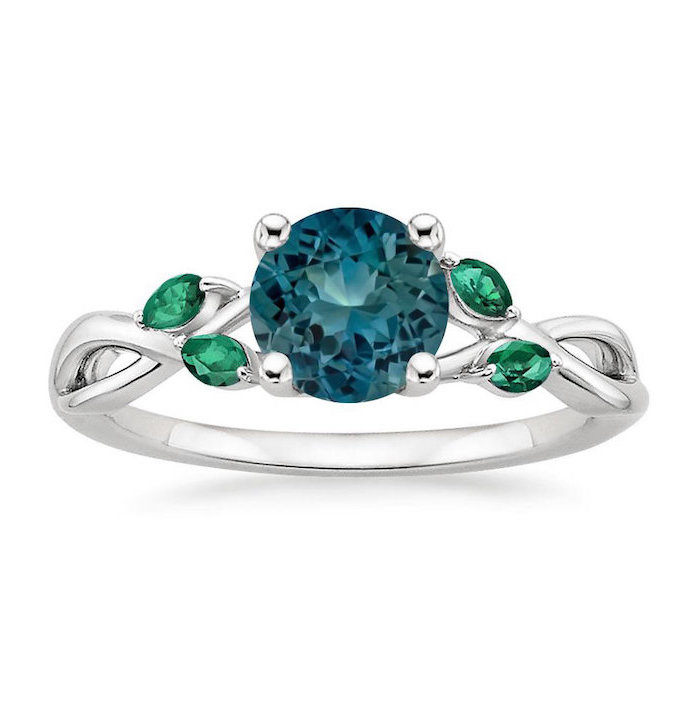 round sapphire, small emerald stones, white gold band, white background, beautiful engagement rings