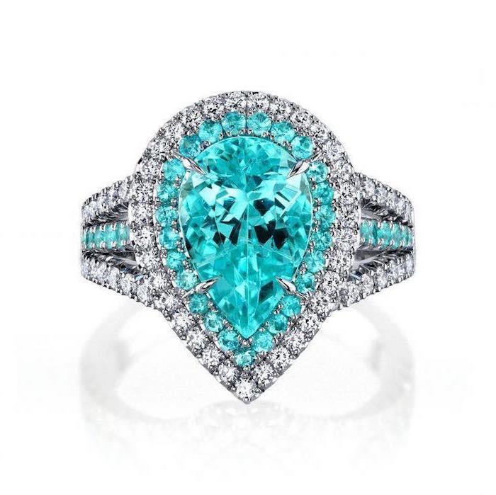 large teardrop emerald stone, diamond studded band, round halo engagement rings, white background