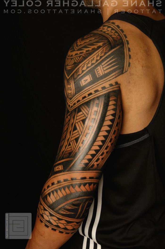 cool small tattoos, large tribal, arm sleeve tattoo, man wearing a black top, standing in front of a black background