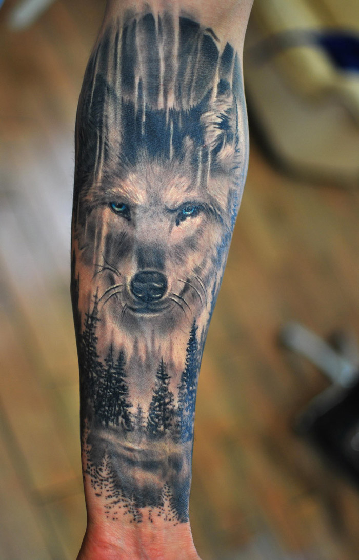 large wolf head, over a forest landscape, forearm tattoo, cool small tattoos, blurred background