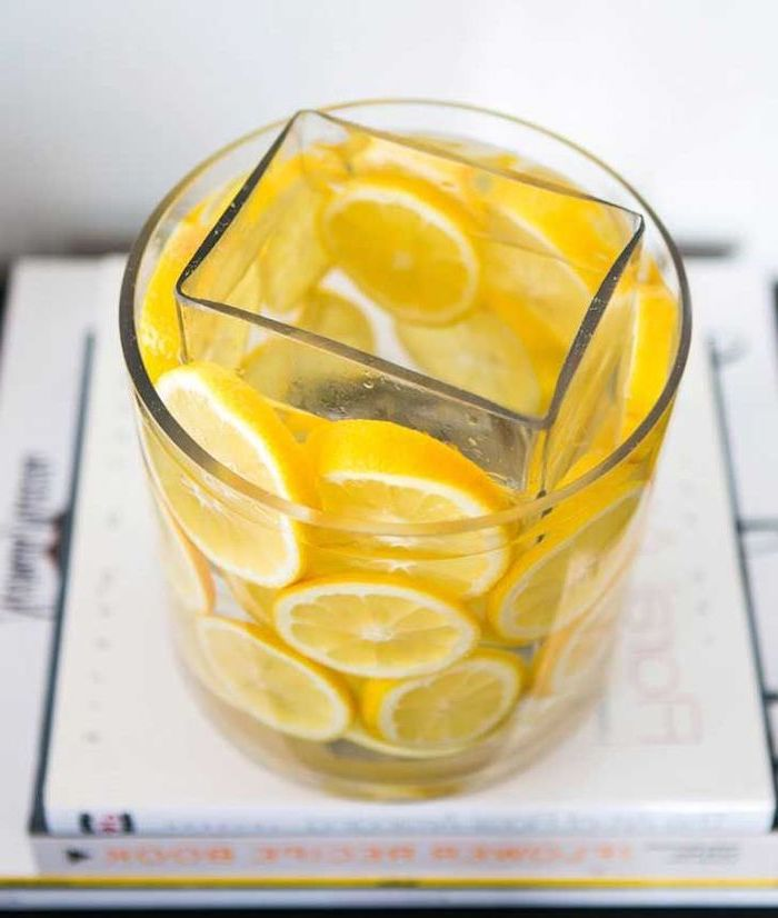 large round vase, filled with lemon slice, smaller square vase inside, silk flower arrangements, on top of books
