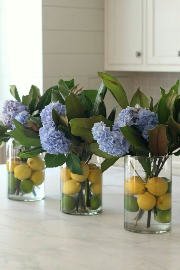 lemons floating in the water, in a round vase, flower arrangement ideas, blue flowers in three vases
