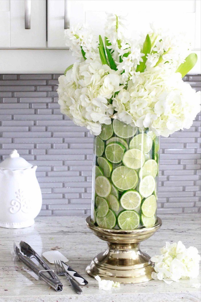 lime slices in a large round vase, white flowers bouquet, on a granite countertop, flower arrangement ideas