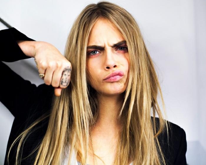 cara delevingne with long blonde hair, lion tattoo, on the finger, finger tattoos for women, black blazer