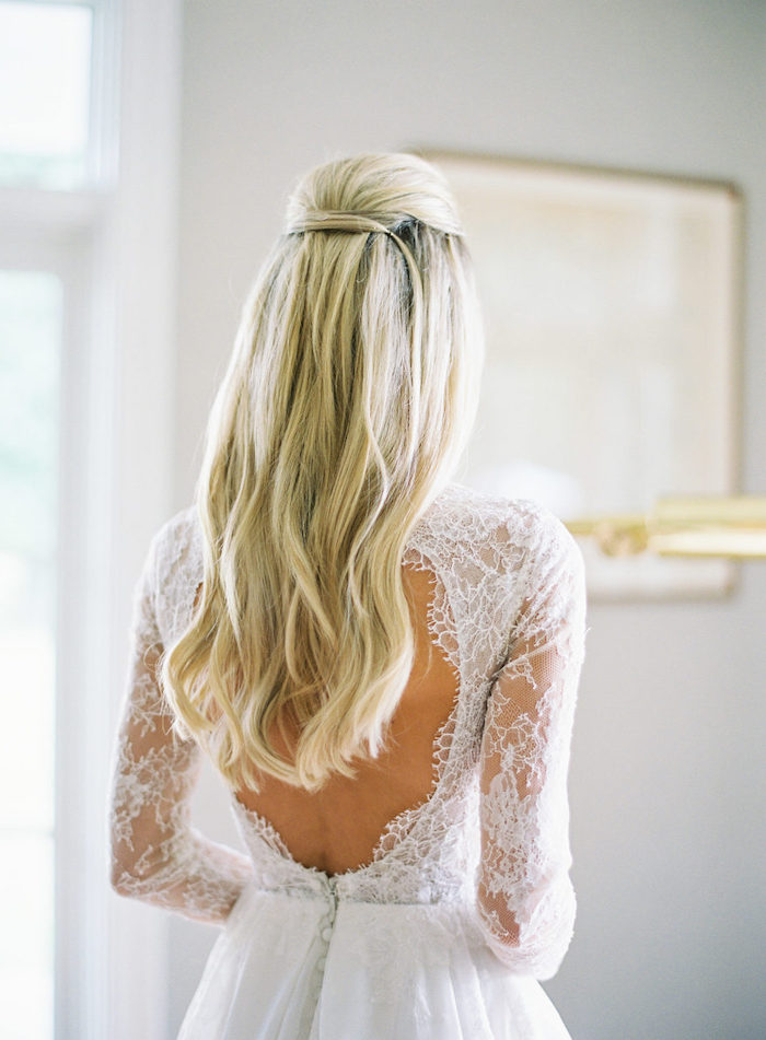 long wavy blonde hair, wedding hairstyle, white dress with lace, blurred background
