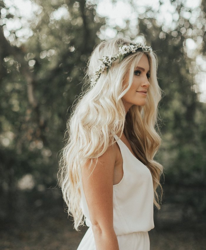 long wavy blonde hair, floral headband, long hair wedding styles, white dress, blurred background