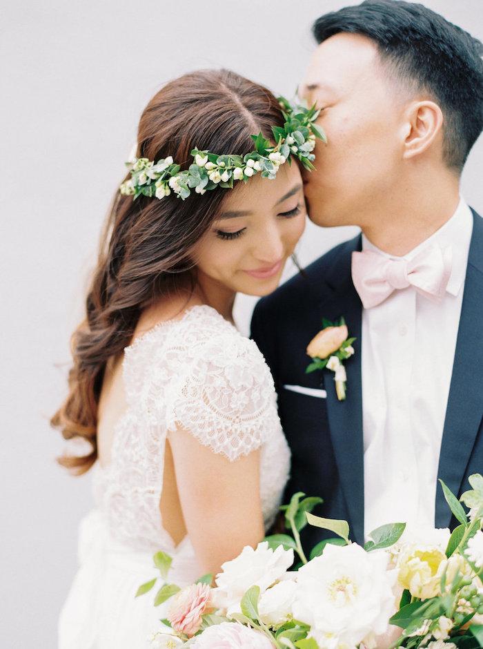 long wavy brown hair, floral headband, long hair wedding styles, man kissing a woman, flower bouquet