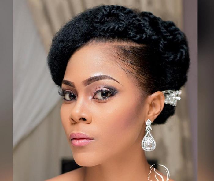 black hair in a low updo, teardrop diamond earrings, wedding hairdos, pearl hair accessory